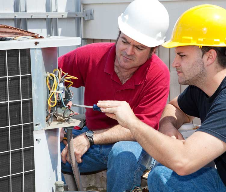 Two HVAC technicians installing a new unit